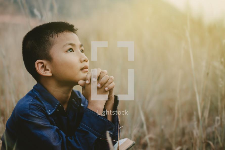 boy praying outdoors