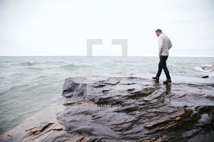 man walking on rocks near a shore
