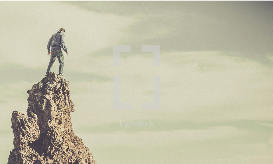 A man standing on the top of a rock formation.