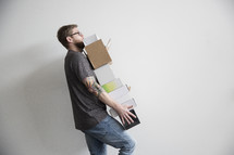 a man carrying a stack of boxes