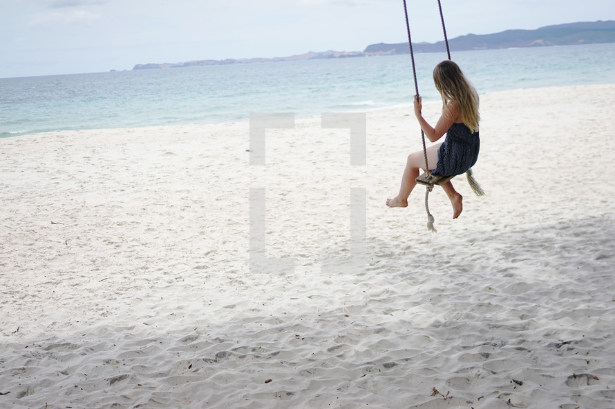 a woman on a rope swing on a beach