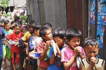 children in line holding bowls praying
