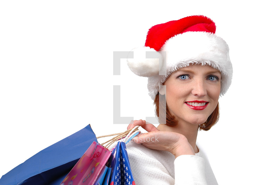 A woman in a Santa hat carrying shopping bags.