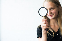 teen girl looking through a magnifying glass