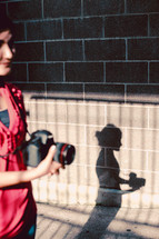 woman and shadow holding a camera