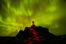 A man standing at the top of a mountain under the glow of star light.