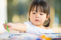 a toddler girl painting