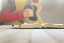 a person playing a guitar and reading a Bible