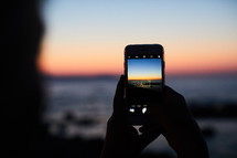 person taking pictures at sunset