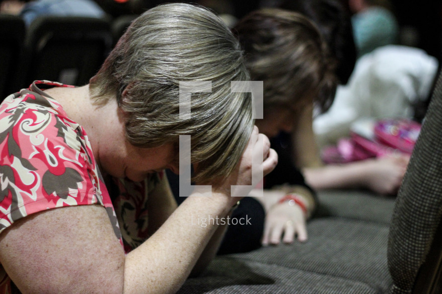 women kneeling in prayer in front of their seats at church