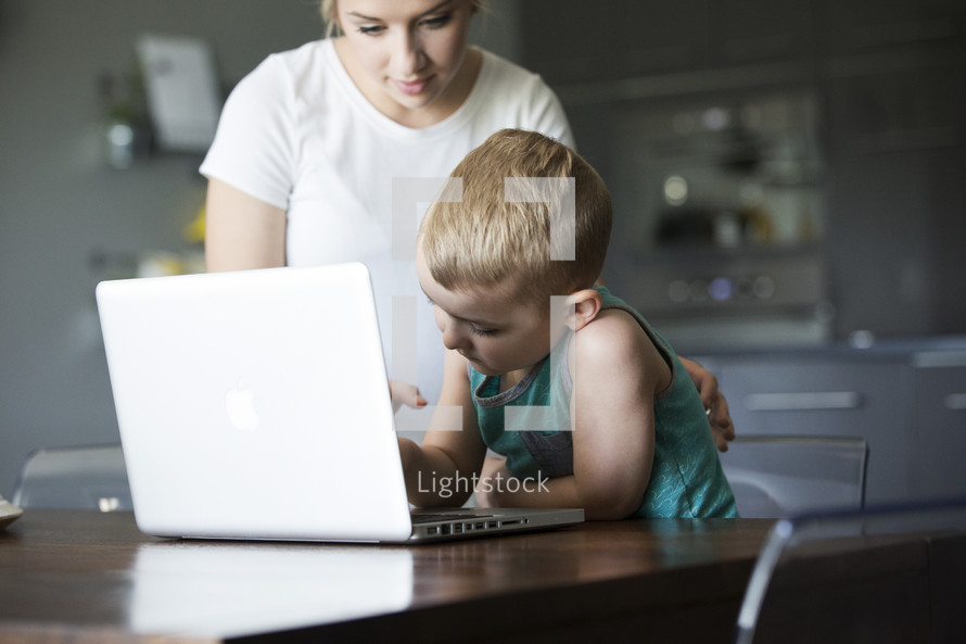 a mother teaching her son to use a computer