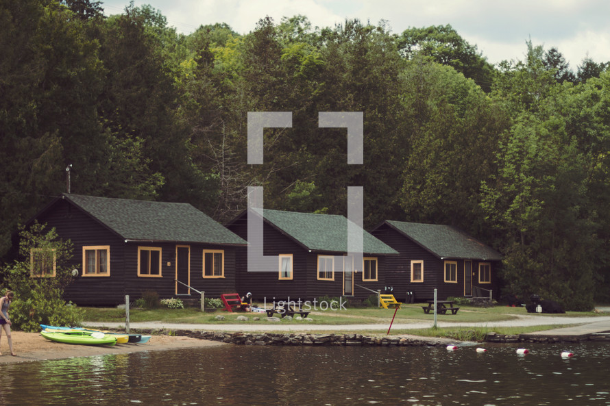 Vintage cabins in a row by a lake.