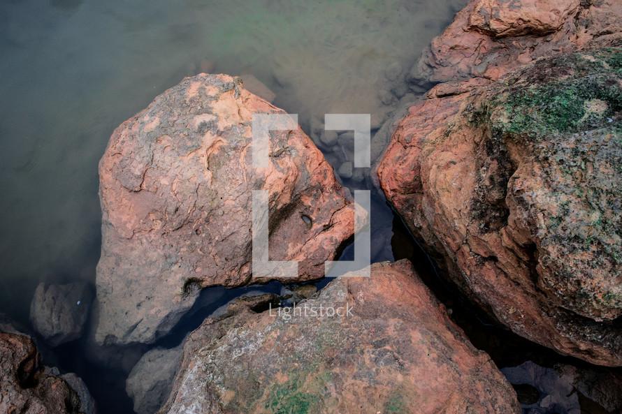 red rocks along a lake shore