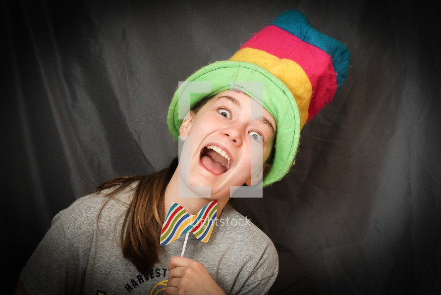 teen girl acting silly with a bow tie and hat