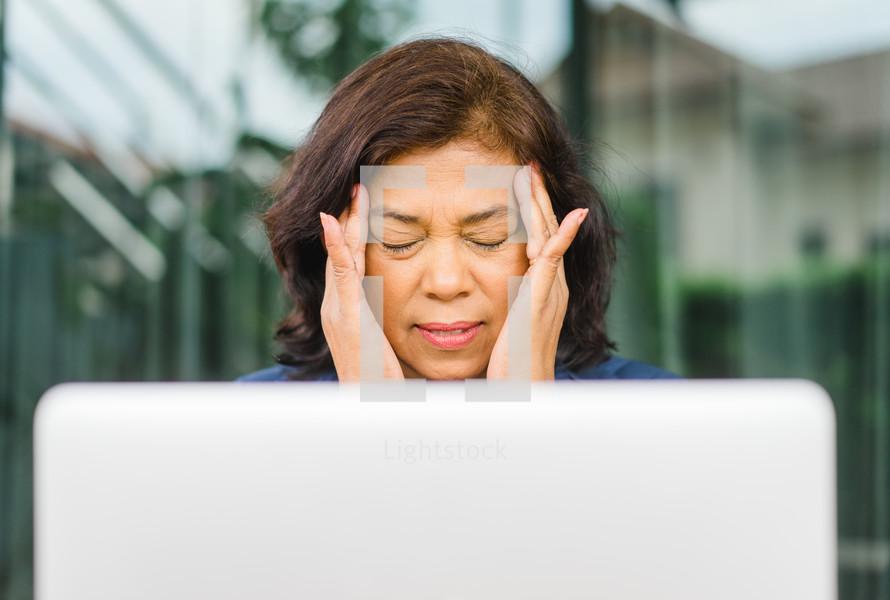 woman sitting behind a computer with a headache