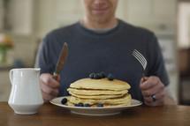man eating pancakes