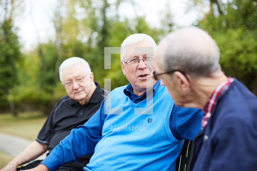 elderly men talking outdoors