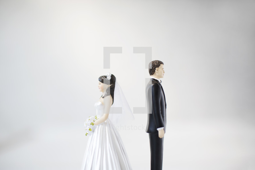 bride and groom figurines standing back to back.