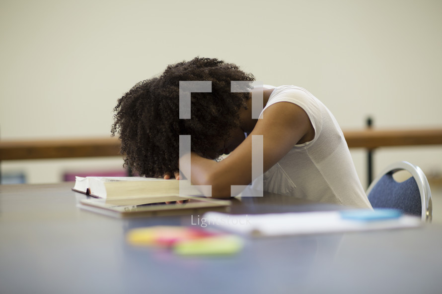 an exhausted woman resting her head on a table