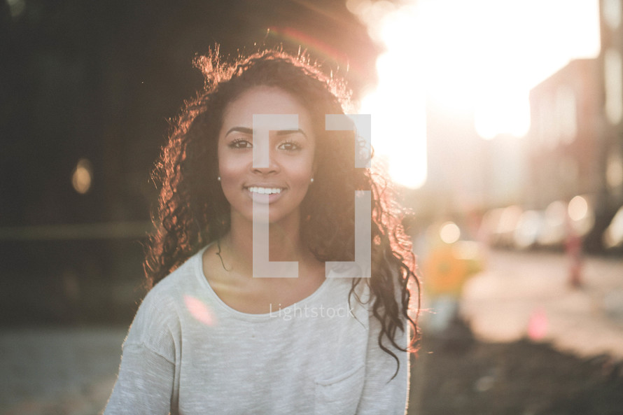 a smiling young African-American woman outdoors under intense sunlight