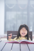 Cute little girl doing homework, reading a book, coloring pages, writing and painting