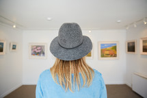 a woman looking at artwork in an art gallery