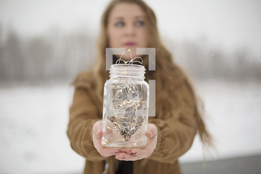 a woman holding a mason jar full of fairy lights