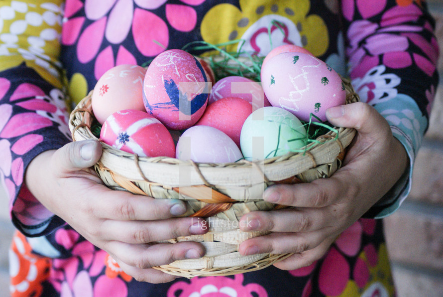 a child holding a basket of Easter eggs
