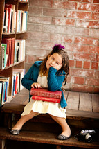 child sitting in a library with a stack of books in her lap and her head resting in her hand
