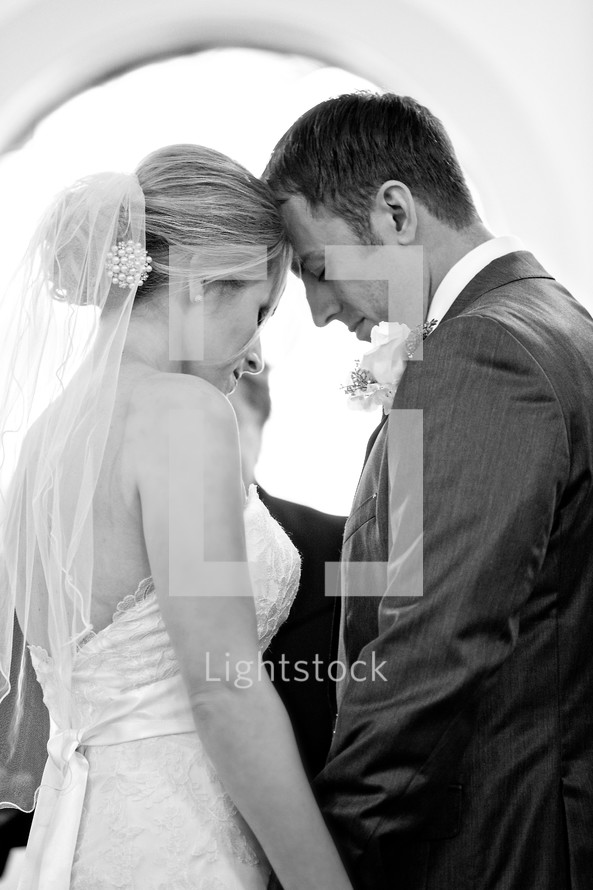 Bride and groom praying together at wedding alter