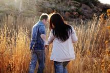 man leading a woman through tall grass
