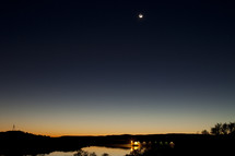 The last bit of sun sets below the horizon to reveal the night sky with moon overhead. A bridge can be seen in the distance.
