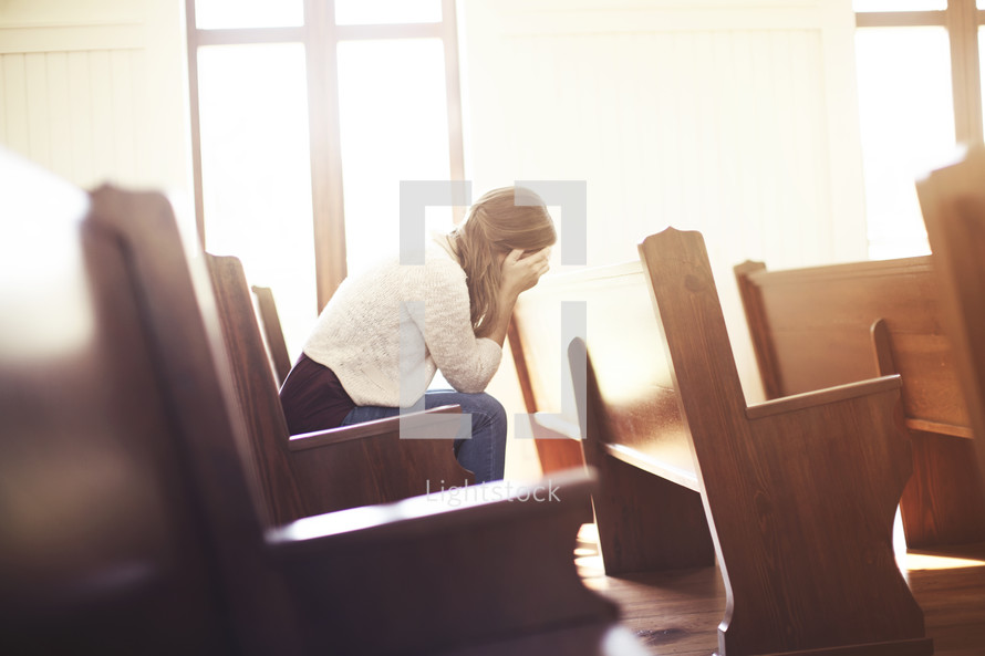 a woman hiding her face in her hands sitting in a church pew
