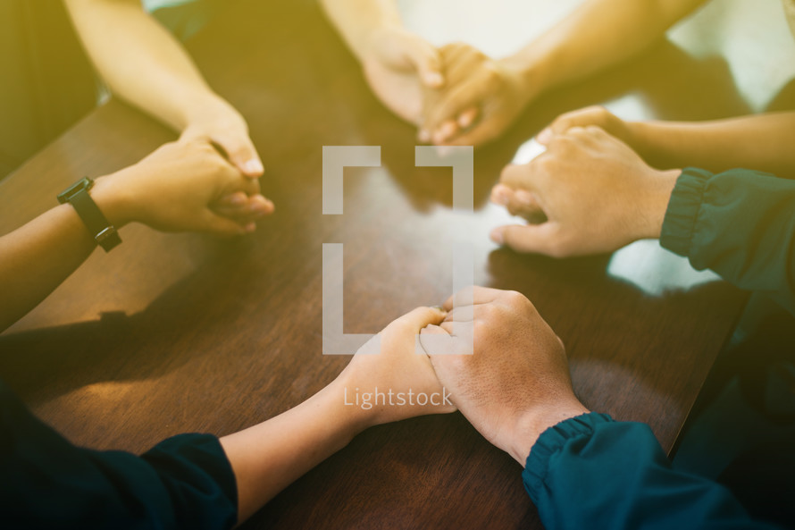 holding hands around a table in a prayer circle