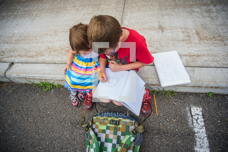a boy drawing in a notebook and sister watching