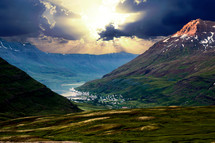 sunlight through the clouds over a coastal town surrounded by mountains