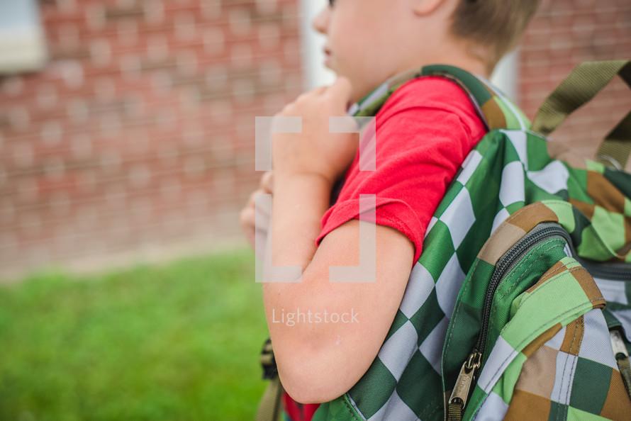 boy walking to school carrying his book bag over his shoulders