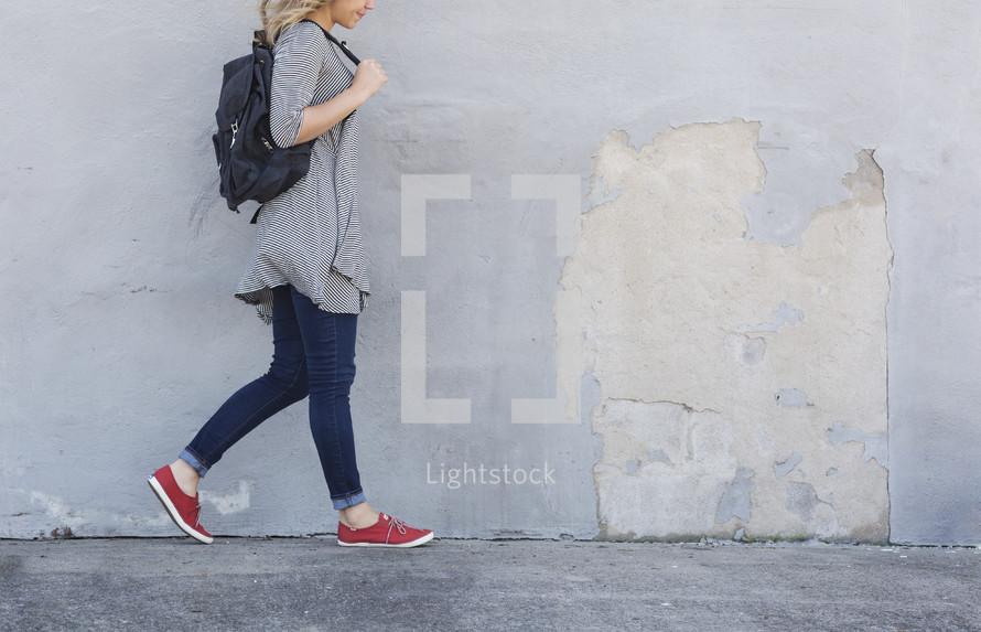 a woman walking on a sidewalk carrying a bag