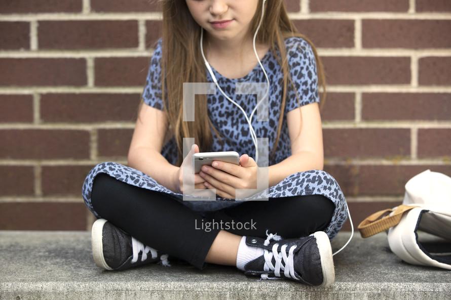 a little girl listening to music on an iPod