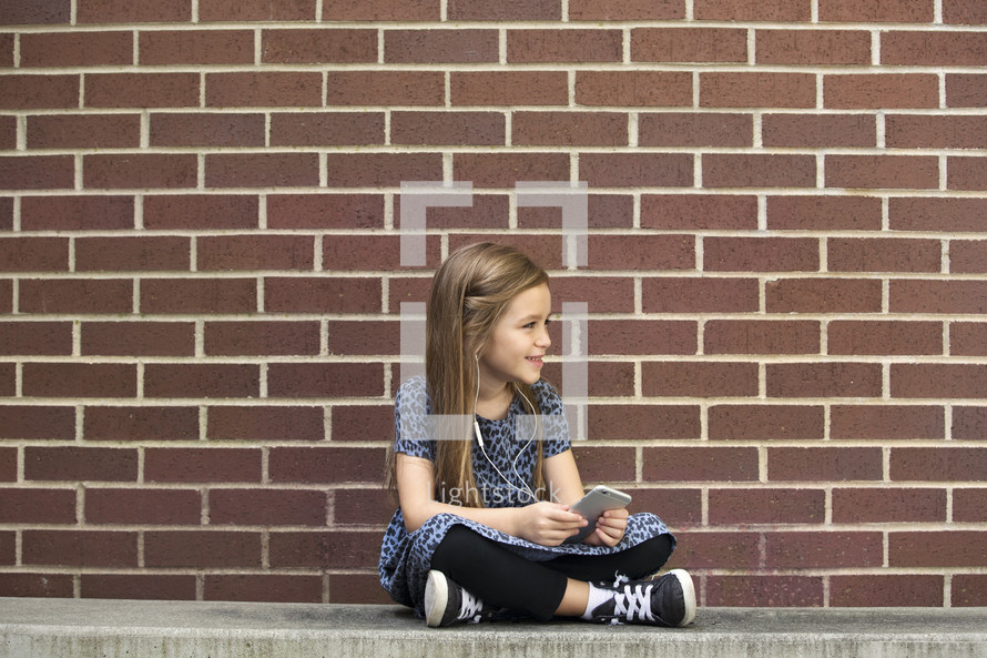 a girl child sitting on a bench listening to an iPod