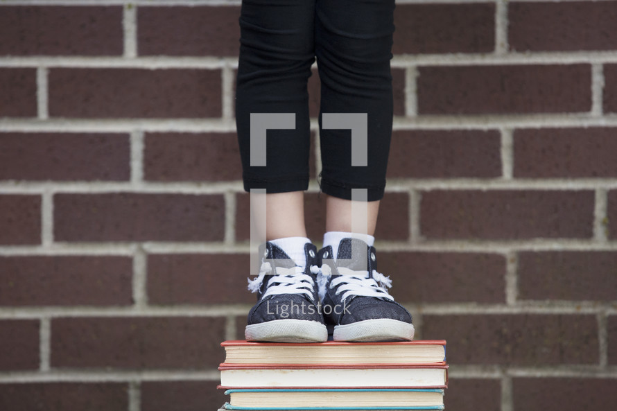 a student standing on a stack of books