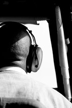 man in headphones looking out a window