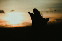 woman with outstretched arms at sunset