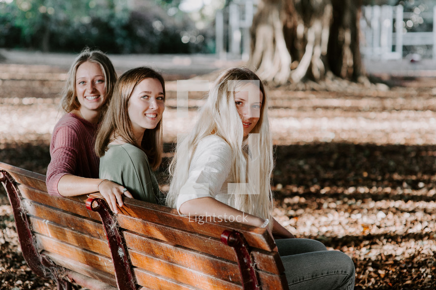 three women sitting on a park bench