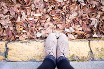 Feet on the curb with autumn leaves.