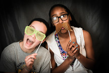 teen girls acting silly with mustaches and sunglasses