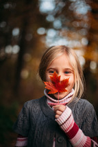 a girl holding a fall leaf in front of her face