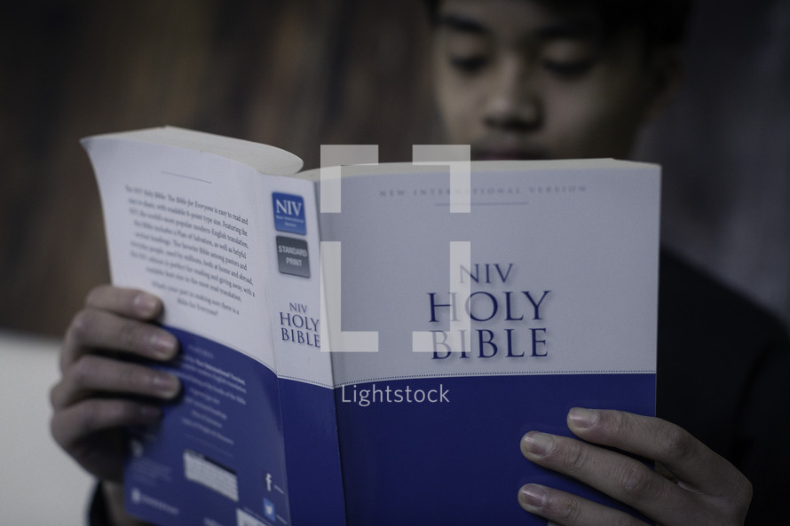 A young man reading a Bible.