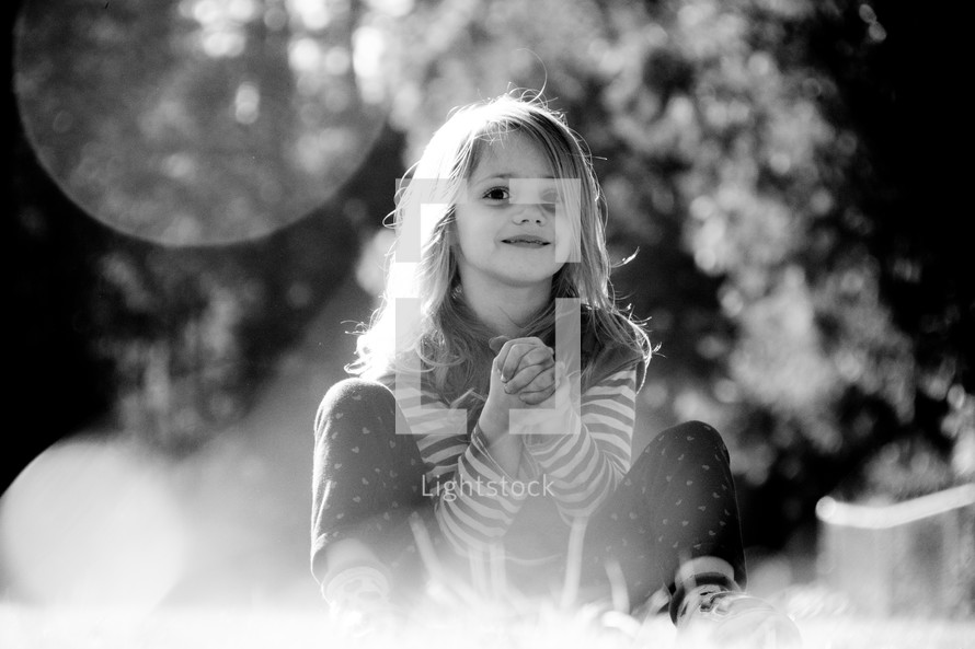 A smiling little girl sitting in sunshine.