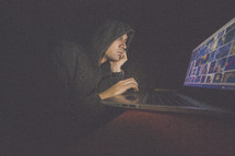 A man in a hooded sweatshirt works on a laptop computer in the dark.